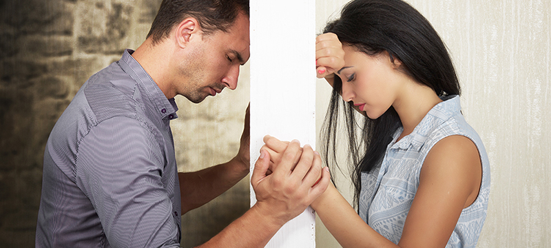 eine scheinbar unüberbrückbare Mauer steht zwischen einem jungen Paar - Beziehungsprobleme Paarberatung